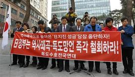 """<p>South Korean activists pay a silent tribute to the victims of the earthquake and tsunami in Japan before holding an anti-Japan rally protesting Japan's sovereignty claim on the Dokdo islets, in front of the Japanese embassy in Seoul, in this March 30, 2011 file photo. The banner reads """"Japan! Withdraw distortions of history (in Japanese history textbooks)!"""" REUTERS/Jo Yong-Hak/Files</p>"""