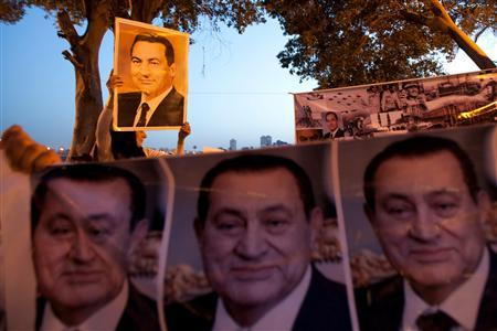 Protesters holding posters of former president Hosni Mubarak chant slogans in support of Mubarak in downtown Cairo April 17, 2011. REUTERS/Youssef Boudlal