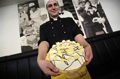 "<p>Confectioner Florian Baecker presents his cake created for the wedding of Prince William and his fiancee Kate Middleton as he stands in front of a photograph of his grandfather holding cakes for the wedding of Prince Charles and Lady Diana at the bakery ""Cafe Victoria"" (named after Britain's Queen Victoria) in Eberbach, 90km south-west of Frankfurt, April 19, 2011. REUTERS/Kai Pfaffenbach</p>"