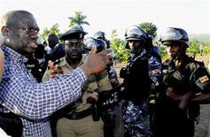 <p>Uganda's Forum for Democratic Change (FDC) leader Kizza Besigye (L) talks to anti-riot policemen before his arrest at Kasangati suburb of the capital Kampala, April 11, 2011. REUTERS/Edward Echwalu</p>