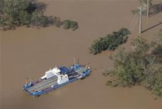 <p>The damaged Moggill ferry sits in flood waters near broken power transmission lines west of Brisbane January 13, 2011. REUTERS/Tim Wimborne</p>