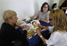 <p>Holocaust survivor Miriam Pe'er Junger (L) points at a post-war photograph of her husband before handing it to a Yad Vashem employee at the Yad Vashem Holocaust History Museum in Jerusalem May 2, 2011. REUTERS/Baz Ratner</p>