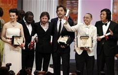 <p>Director Apichatpong Weerasethakul (2nd R) pose with director Lee Chang-dong (R), actor Javier Bardem (3rd R), director Mathieu Amalric(3rd L), director Mahamat-Saleh Haroun and actress Juliette Binoche (L) after winning the Palme d'Or award for the film Lung Boonmee Raluek Chat (Uncle Boonmee Who Can Recall his Past Lives) during the award ceremony of the 63rd Cannes Film Festival May 23, 2010. REUTERS/Eric Gaillard</p>