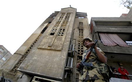 An Egyptian army guard stands outside the Saint Mary Church, which was set on fire during clashes between Muslims and Christians on Saturday in the heavily populated area of Imbaba in Cairo May 8, 2011. REUTERS/Mohamed Abd El-Ghany
