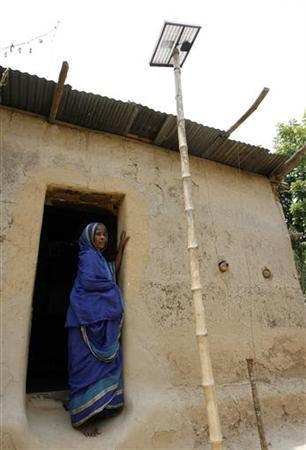 A woman stands in the doorway of her mud house next to a solar system panel near Patulia village in the Gazipur district north of capital Dhaka in this May 5, 2007 photo. REUTERS/Rafiqur Rahman