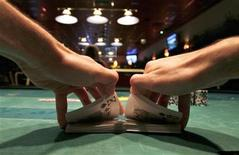<p>A dealer shuffles a deck of cards during a poker game at a casino in Budapest September 15, 2009. REUTERS/Katoly Arvai</p>