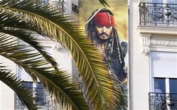 """<p>Постер с изображением Джонни Деппа в роли Джека Воробья из """"Пиратов Карибского моря"""" на здании гостиницы в Каннах, 9 мая 2011 года. Общие кассовые сборы четвертой части """"Пиратов Карибского моря"""" за первые дни проката составили $346,4 миллиона, что позволило картине установить рекорд по результатам дебюта за пределами Северной Америки, сообщила киностудия. REUTERS/Yves Herman</p>"""