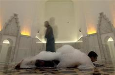 <p>An attendant walks past a customer receiving a soap massage at the newly restored Roxelana's hamam in Istanbul May 12, 2011. REUTERS/Osman Orsal</p>