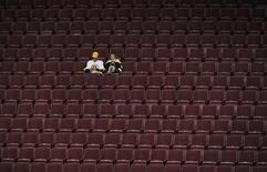<p>A pair of Boston Bruins fans sit alone after their team was defeated in overtime by the Vancouver Canucks during Game 2 of the NHL Stanley Cup hockey playoff game in Vancouver, British Columbia, June 4, 2011. REUTERS/Andy Clark</p>