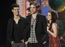 """<p>Taylor Lautner (L), Robert Pattinson and Kristen Stewart introduce a clip from """"The Twilight Saga: Breaking Dawn"""" at the 2011 MTV Movie Awards in Los Angeles, June 5, 2011. REUTERS/Mario Anzuoni</p>"""