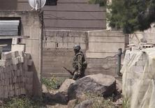 <p>Сирийский солдат в поселке около ливано-сирийской границы, 19 мая 2011 года. Более 120 сотрудников сирийских спецслужб погибли в боях с боевиками, сообщило в понедельник государственное телевидение Сирии. REUTERS/Mohamed Azakir</p>