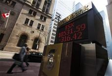 <p>People walk by a sign displaying TSX information in Toronto, August 17, 2009. REUTERS/Mark Blinch</p>