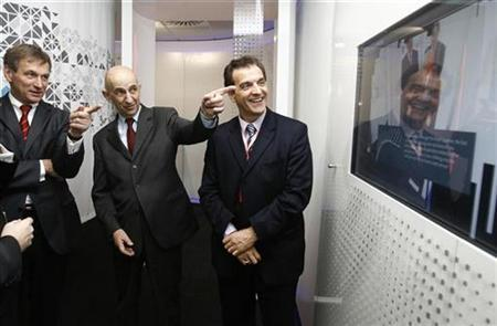 Louis Gallois (C), chief executive officer of European Aeronautic Defence and Space company (EADS), Stefan Zoller (L), CEO of the defense and security division, and Jean Botti, chief technology officer look at a reading after passing through a body scanner designed and built by EADS during a tour of their facility in Newport, south Wales January 13, 2009. REUTERS/Andrew Winning