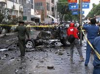 <p>People take picture of a damaged car after a blast in Mandalay June 24, 2011. REUTERS/Stringer</p>