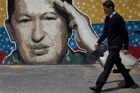 A man walks past graffiti depicting Venezuelan President Hugo Chavez in Caracas, June 27, 2011. REUTERS/Carlos Garcia Rawlins