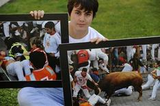 <p>Chilean Alonso Ceardi poses with two pictures that show when he was severely gored during the running of the bulls at the 2010 San Fermin festival in Pamplona, in Oviedo July 4, 2011. REUTERS/Eloy Alonso</p>