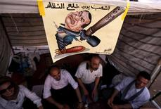 <p>Protesters sit in a makeshift tent near a poster depicting former President Hosni Mubarak in Tahrir square, Cairo July 10, 2011. REUTERS/Mohamed Abd El-Ghany</p>