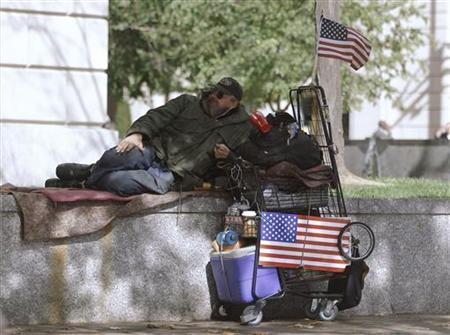 A homeless man lies on a retaining wall on Pennsylvania Avenue NW, Washington, October 6, 2010. REUTERS/Jason Reed