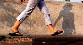 <p>A woman walks with flip flops in Washington, July 15, 2003. REUTERS/William</p>