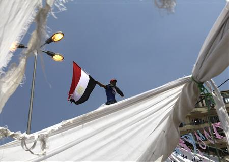 A man waves an Egyptian flag near tents in Tahrir Square in Cairo July 15, 2011. REUTERS/Asmaa Waguih