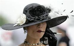 <p>A woman smokes a cigarette at Churchill Downs in Louisville, Kentucky, May 7, 2011. REUTERS/John Sommers II</p>