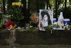 <p>La cantante de soul Amy Winehouse, quien murió inesperadamente a los 27 años, recibió varios tributos el sábado, desde admiradores comunes de todo el mundo y de estrellas de la música que van desde Tony Bennett al productor Mark Ronson. En la foto, flores, fotografas, cigarros y botellas de licor recuerdan a la artista en la puerta de su hogar en Londres, el 24 de julio del 2011. REUTERS/Stefan Wermuth (RUNIDO)</p>