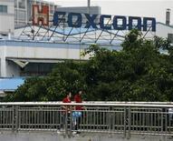 <p>Foto de archivo de un grupo de empleados de Foxconn a las afueras de una planta de la firma en Longhua, China, jun 2 2010. La empresa taiwanesa Foxconn Technology Group, conocida por el montaje de iPhone e iPad de Apple en China, planea usar más robots, y un informe dijo que la compañía usará un millón de ellos en los próximos tres años, para hacer frente al aumento de costos laborales. REUTERS/Bobby Yip</p>