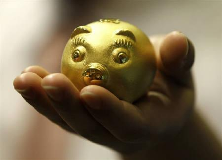 An employee of a jewellery shop holds a 112.5 gram-weight gold pig during a photo opportunity at a jewellery shop at the Shinsegae department store in Seoul August 1, 2011. REUTERS/Jo Yong-Hak
