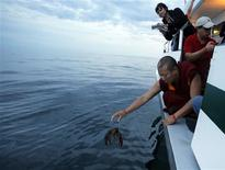 """<p>Buddhist monk Geshe Tenley releases a lobster back into the ocean during """"Chokhor Duchen"""", or the anniversary of Buddha's turning of the Dharma Wheel, from a boat in the waters off Gloucester, Massachusetts August 3, 2011. REUTERS/Brian Snyder</p>"""
