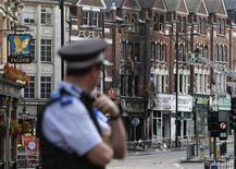 <p>A police officers stands near a burnt out shop in Clapham Junction, in south London August 9, 2011. REUTERS/Stefan Wermuth</p>