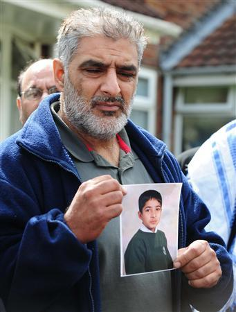 Tarmiq Jahan holds a picture of his son Haroon Jahan after he was killed killed by a car along with two other men in the Winson Green area of Birmingham, central England August 10, 2011. REUTERS/Darren Staples
