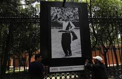 """<p>Foto de archivo de unas personas colocando una fotografía del actor Mario Moreno """"Cantinflas"""" en una muestra callejera en Ciudad de México, jul 25 2011. En las calles de la capital, en el metro, la televisión y el cine, los mexicanos ríen nostálgicos estos días recordando a Mario Moreno """"Cantinflas"""", considerado uno de los mayores comediantes del siglo pasado y de cuyo nacimiento se cumplen el viernes 100 años. REUTERS/Carlos Jasso</p>"""