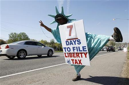 Bogi Johannes, who is dressed as the Statue of Liberty, tries to attract business for Liberty Tax preparers in Falls Church, Virginia April 8, 2010. REUTERS/Kevin Lamarque