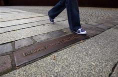 <p>A person walks across the plaque and a line of bricks that show where the Berlin Wall used to stand at the Berlin Wall memorial site in Bernauer Strasse, August 9, 2011. REUTERS/Thomas Peter</p>