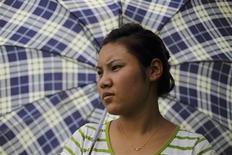 <p>Stateless Nina Tamang, 18, is seen as she covers herself from an umbrella while she gaze her cattle's near her home at the outskirts of Nepal's capital August 14, 2011. REUTERS/Navesh Chitrakar</p>