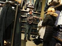 <p>A man tries on a shirt while shopping at a clothing store in New York, December 14, 2010. REUTERS/Shannon Stapleton</p>