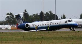 <p>Workers take photographs of a United Express plane after it skidded off the runway at the Ottawa International Airport September 4, 2011. REUTERS/Chris Wattie</p>