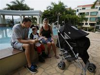 <p>Daniel Mullin (L) and his wife Cathryn listen to three-year-old Harry as their newborn Jake sleeps in the stroller in Hong Kong September 3, 2011. As global companies expand in Asia, financial hubs such as Hong Kong are suffering a shortage of international school places that may blunt the city's competitive edge against regional rivals including Singapore. For the Mullins who moved to Hong Kong from Britain in February, the stresses of finding a school for older son Harry have meant they'll be taking no chances with newborn Jake by putting him straight on a waiting list. Picture taken September 3, 2011. REUTERS/Bobby Yip</p>