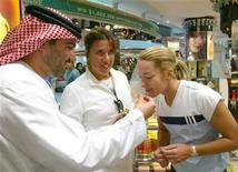 <p>Tennis tournament director Saleh Tahlak (L) allows tennis player Justine Henin-Hardenne of Belgium (R) to smell a traditional Arabic perfume while Jennifer Capriati (C) of the U.S. watches during a visit to the duty free shops at the Dubai International Airport February 24, 2004. REUTERS/Anwar Mirza</p>