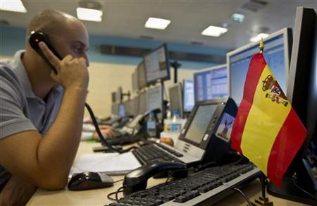 A Spanish trader talks on a telephone during a bond auction at a trading floor in Madrid's financial district August 4, 2011. REUTERS/Paul Hanna