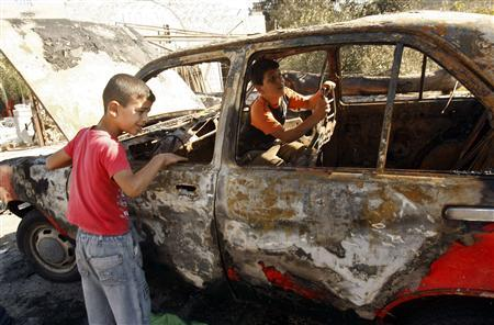 Palestinian brothers Ahmad (R) and Mohmoud Mleitat inspect their father's car after is was torched in the West Bank village of Beit Furik near Nablus September 15, 2011. REUTERS/Abed Omar Qusini