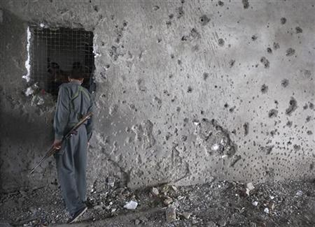 An Afghan policeman looks at the bodies of Taliban insurgents (behind the wall) who were killed after the building that they took over was recaptured by NATO and Afghan security forces near the U.S. embassy in Kabul, September 14, 2011. REUTERS/Ahmad Masood