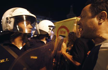 An anti-austerity protester shouts at police officers outside the Greek parliament following an unscheduled cabinet meeting in Athens September 18, 2011. REUTERS/Yannis Behrakis