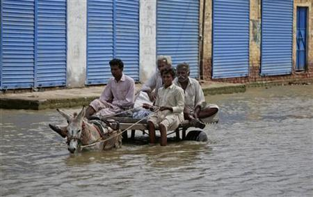 Residents on donkey cart ride past closed shops through a flooded street in the Badin district of Pakistan's Sindh province September 18, 2011. REUTERS/Akhtar Soomro