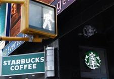 <p>A walk sign flashes in Times Square in front of a store bearing the new Starbucks logo in New York March 8, 2011. REUTERS/Lucas Jackson</p>