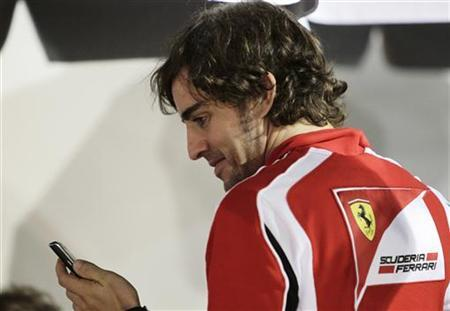 Ferrari Formula One driver Fernando Alonso of Spain smiles as he looks at a message on a mobile phone at the paddock of the Singapore F1 Grand Prix at the Marina Bay street circuit, September 22, 2011.   REUTERS/Tim Chong