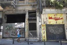 <p>A man walks in front of a row of closed shops in central Athens June 24, 2011. REUTERS/John Kolesidis</p>