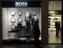 <p>A man looks at a shop window outside the Hugo Boss showroom inside a shopping mall in Mumbai August 23, 2011. REUTERS/Danish Siddiqui</p>