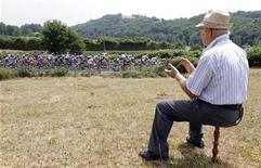 <p>An elderly man looks as the pack rides during the tenth stage of the Tour de France 2011 cycling race from Aurillac to Carmaux July 12, 2011. REUTERS/Pascal Rossignol</p>
