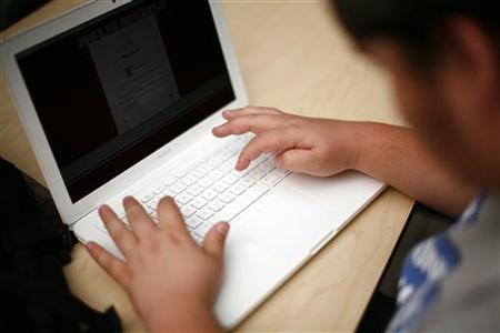 A student sets up a laptop computer on the first day of school at Joplin High School in Joplin, Missouri August 17, 2011. REUTERS/Eric Thayer